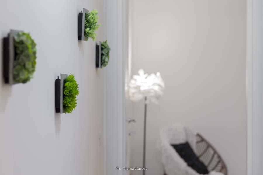 decorazione murale con piante finte lungo un corridoio bianco in lontananza sfocato un lampada da terra e una poltrona