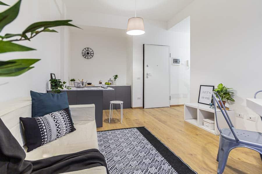 piccolo open space allestito con home staging colore bianco e nero con parquet naturale a terra