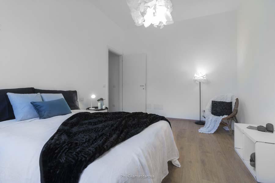 camera da letto con plaid nero, cuscini turchesi e tre lampade accese