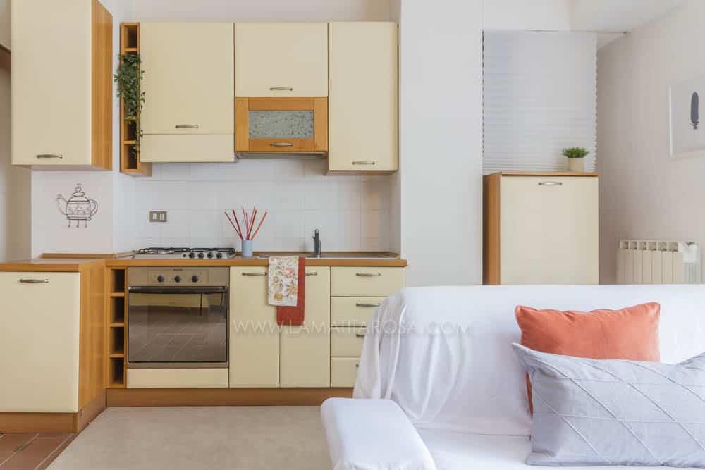 cucina gialla e legno sullo sfondo con canovacci arancioni. in primo piano divano bianco con cuscini arancioni e grigi