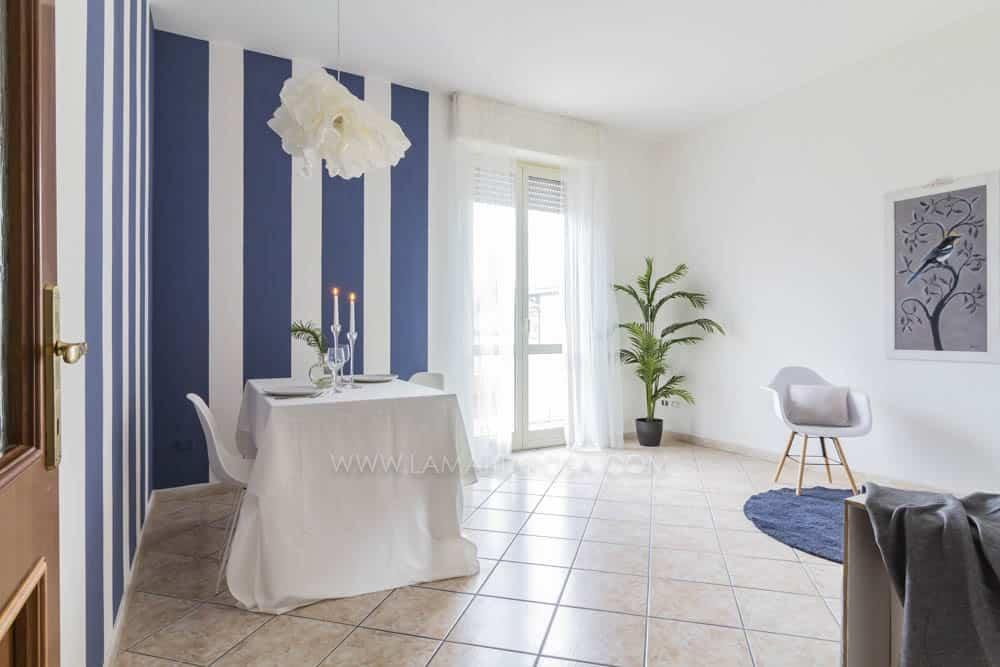 soggiorno con parete a righe verticali blu e bianche, tavola imbandita con candelabri e lampadario